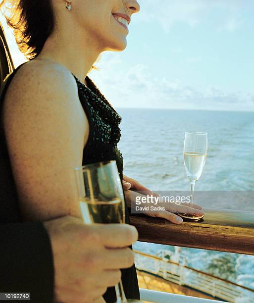 couple having champagne on cruise ship - mid section stock photos and pictures