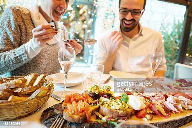 couple having christmas dinner in a restaurant - antipasto stock pictures, royalty-free photos & images