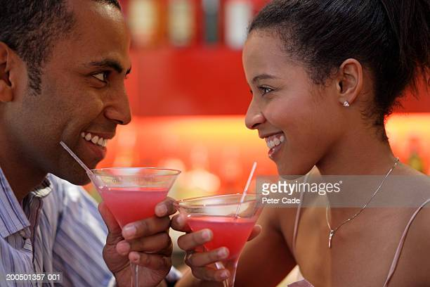 Couple having cocktails, smiling, side view
