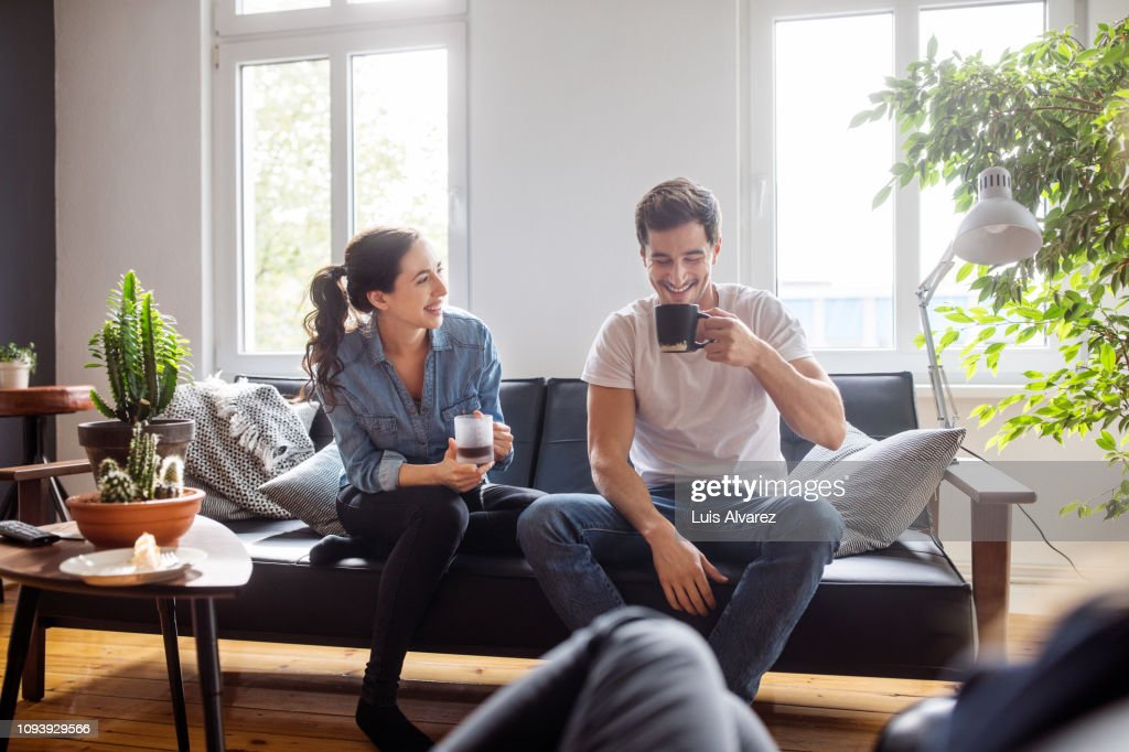 Couple having coffee together in living room : Stock Photo