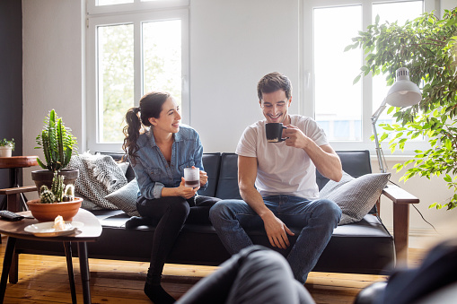 Couple having coffee together in living room - gettyimageskorea
