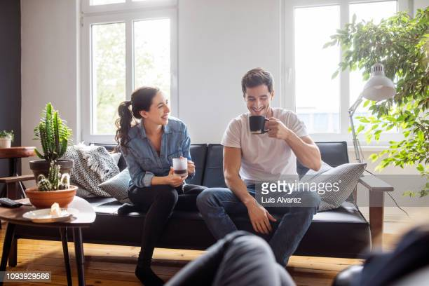 couple having coffee together in living room - couple photos et images de collection
