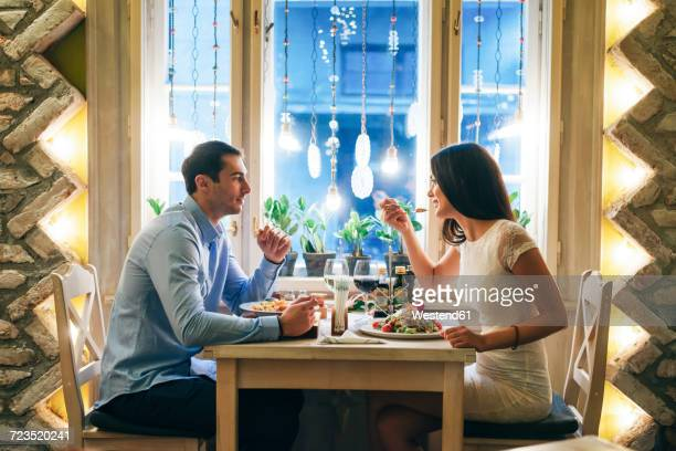 couple having dinner in a restaurant - man eating woman out - fotografias e filmes do acervo