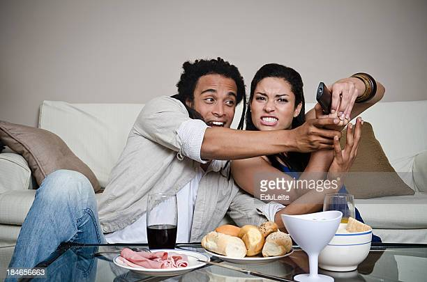Couple having dinner in front of TV fighting over the remote