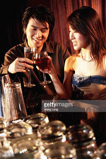 couple having drinks at night club - clubkleding stockfoto's en -beelden