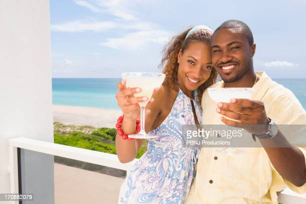 couple having drinks on balcony - margarita beach stock photos and pictures