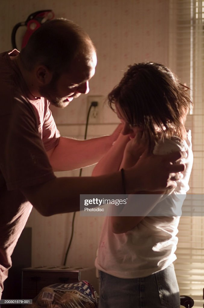 Couple having fight in kitchen, man holding shoulders of woman : Stock Photo