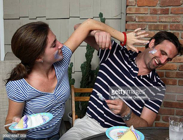 Couple having food fight at outdoor table