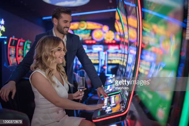 couple having fun and drinking wine at casino - gambling table stock pictures, royalty-free photos & images