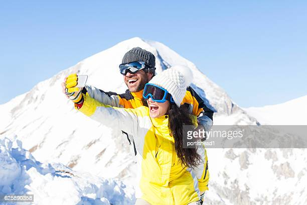 Couple having fun and making selfie in the snow