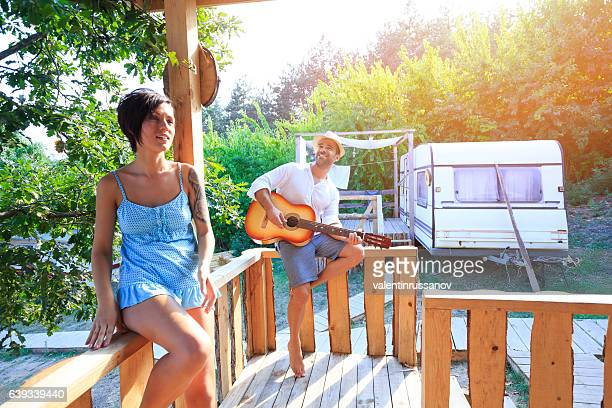 Couple having fun and playing guitar on pavilion