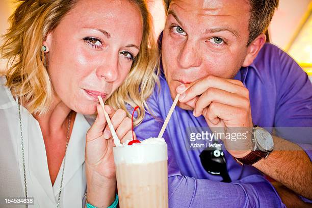 A couple having fun at a diner with a milkshake.
