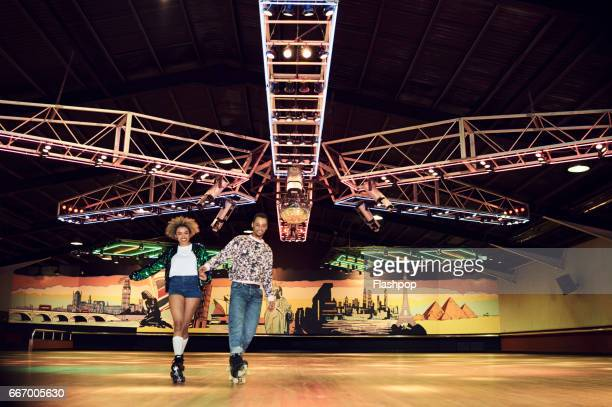 couple having fun at roller disco - roller skating stock pictures, royalty-free photos & images