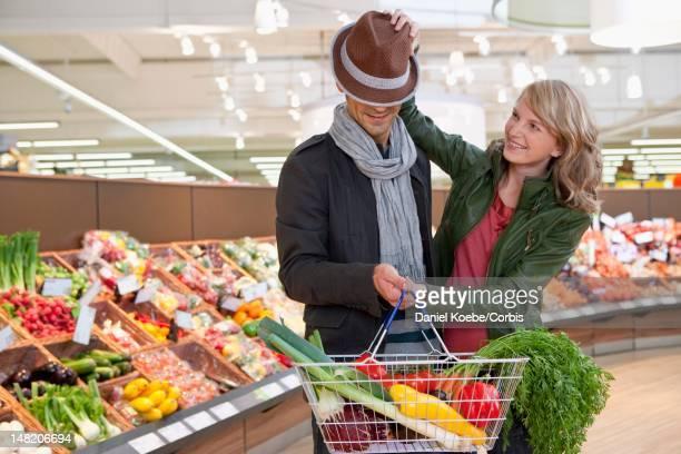 Couple having fun at shopping in supermarket
