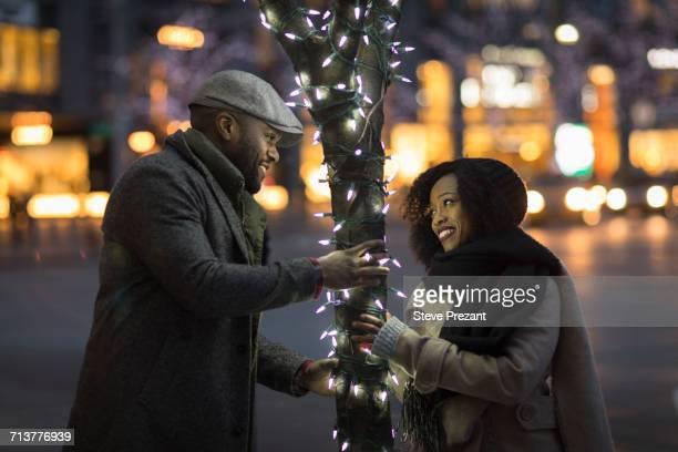 couple having fun by illuminated tree in city at night, new york, usa - nur erwachsene stock-fotos und bilder