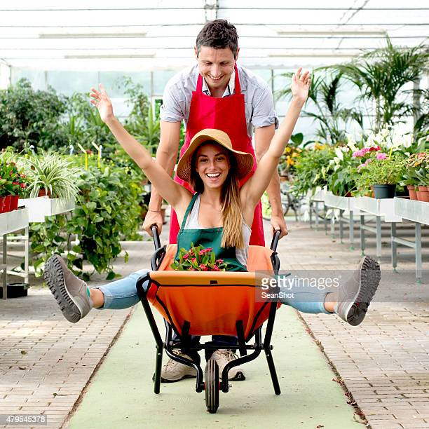 couple having fun in a flower shop - wheelbarrow stock photos and pictures