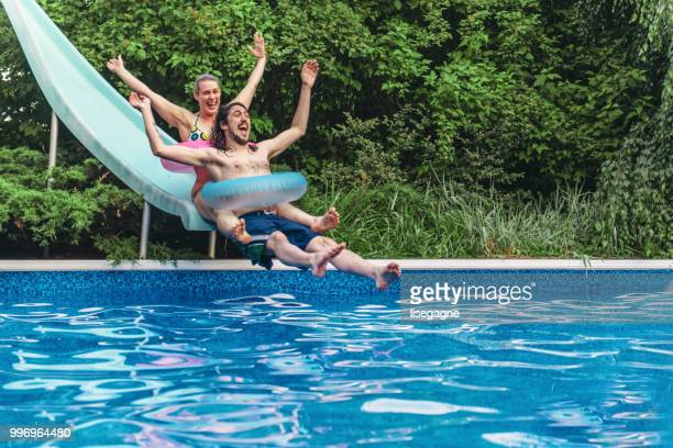 couple having fun in a swimming pool during summer day - sliding stock pictures, royalty-free photos & images