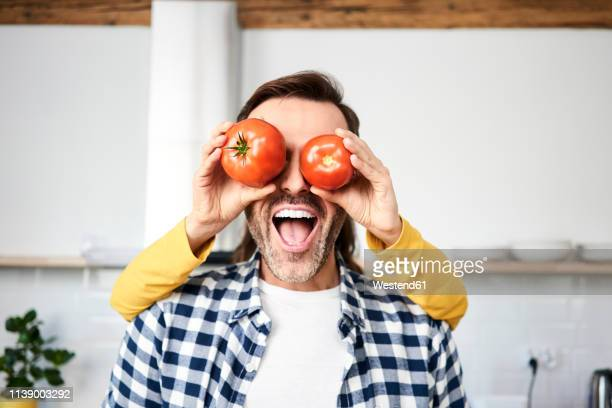 couple having fun in the kitchen, playing with tomatoes - anthropomorphic stock pictures, royalty-free photos & images