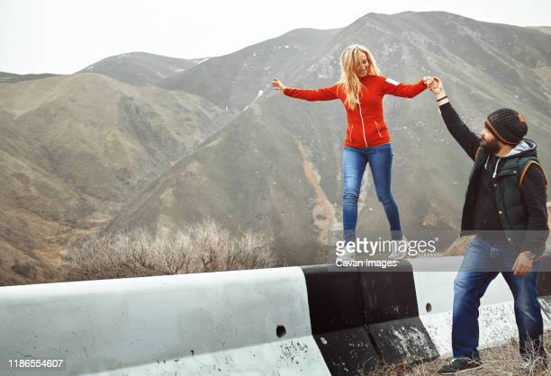 couple having fun in the mountain area - doing a favor stock pictures, royalty-free photos & images