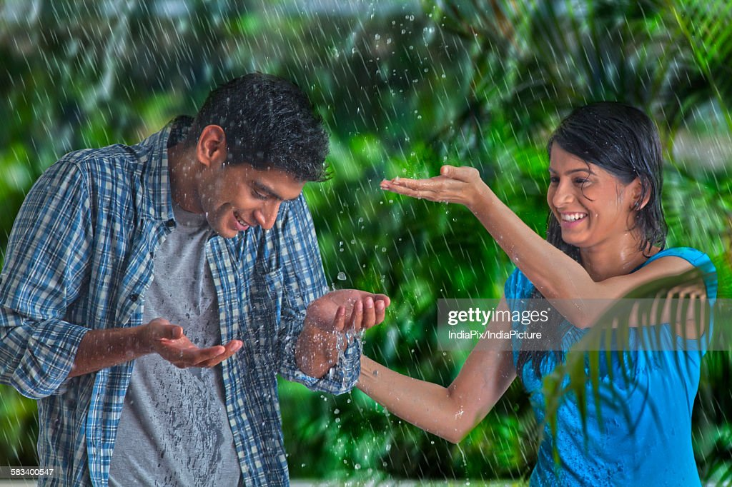 Couple having fun in the rain : Stock Photo
