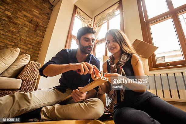 Couple Having Fun Moving In and Assembling Furniture