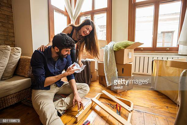 couple having fun moving in and assembling furniture - unpacking stock pictures, royalty-free photos & images