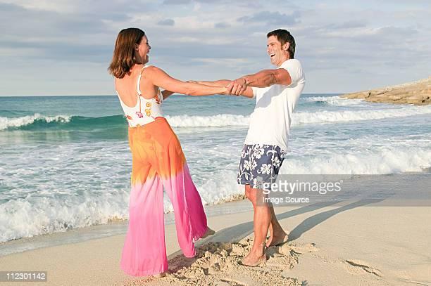 カップルはビーチでお楽しみください。 - タイダイ柄 ストックフォトと画像