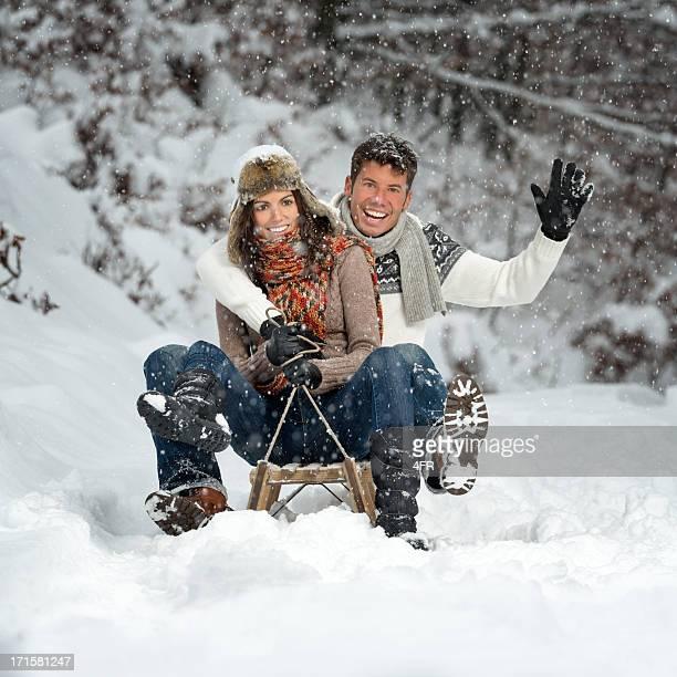 Paar, die Spaß an einem Schlitten mit echten Schneeflocken