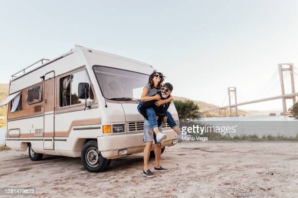 couple having fun outside of a campervan - stock photo - holiday stock pictures, royalty-free photos & images