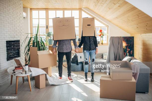 Couple having fun with boxes in new home