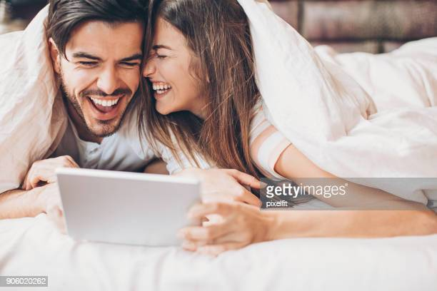 Couple having fun with digital tablet in bed