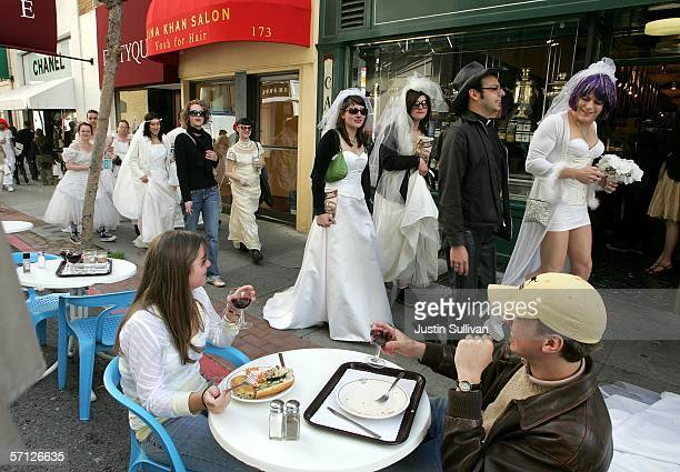 A couple having lunch at an outdoor cafe looks on as a flash mob group calling themselves the Brides of March March 18 2006 in San Francisco The...