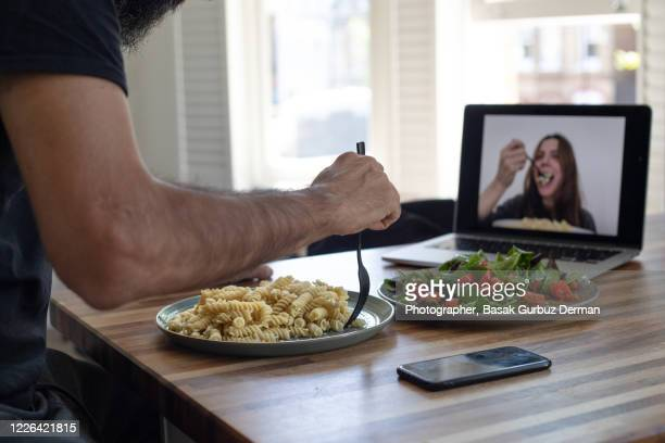 couple having lunch while practicing social distancing using video conferencing technology - friendship stock pictures, royalty-free photos & images