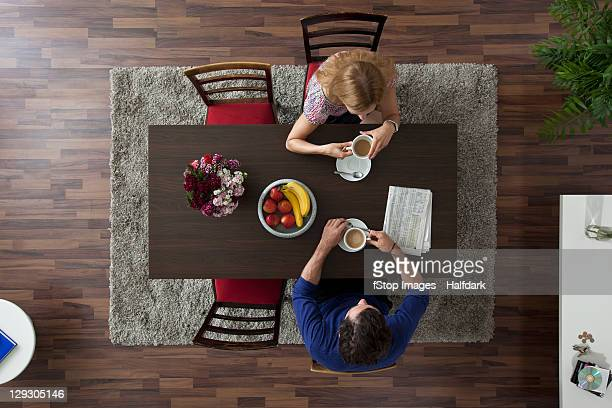A couple having morning coffee together at a dining room table, overhead view