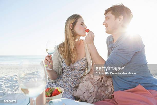 Couple having picnic on beach, man feeding woman strawberry