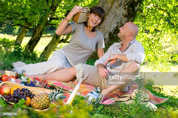 'Couple having picnic under tree, listening to radio'
