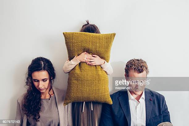 Couple having relationship conflict with their daughter hiding her face behind cushion