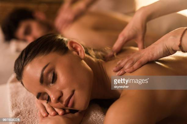 couple having relaxing back massage at beauty spa. - massaggi foto e immagini stock