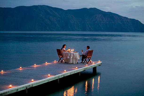 couple having romantic dinner date on pier - couples romance stock pictures, royalty-free photos & images
