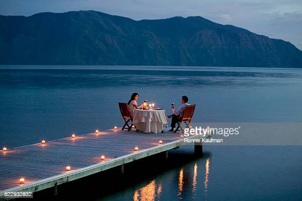couple having romantic dinner date on pier - warmes abendessen stock-fotos und bilder