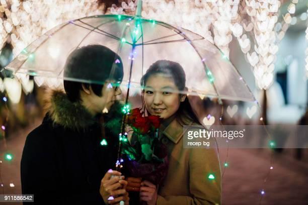 夜の傘の下で Romatic 時間を持っているカップル