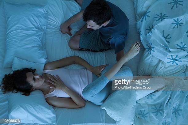 Couple having serious conversation in bed