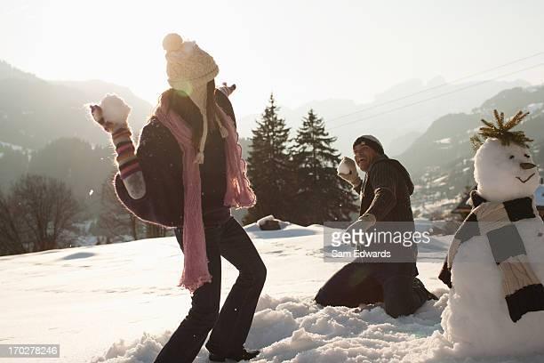 Paar bei einer Schneeballschlacht