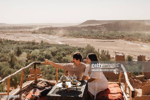 couple having tea on a balcony overlooking the palm grove - grove_(nature) stock pictures, royalty-free photos & images