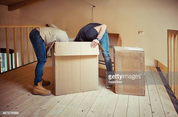 Couple having their heads inside a moving box during a move