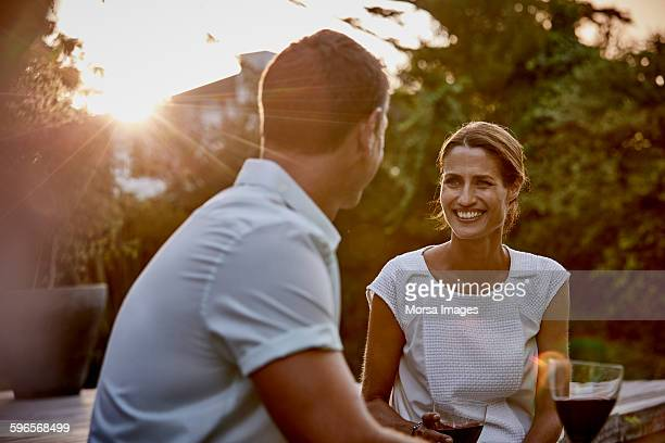Couple having wine on floorboard