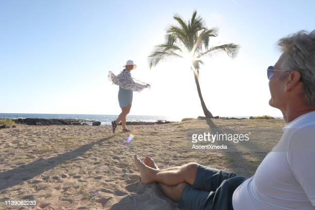 couple head towards beach and palm tree - blue shorts stock pictures, royalty-free photos & images