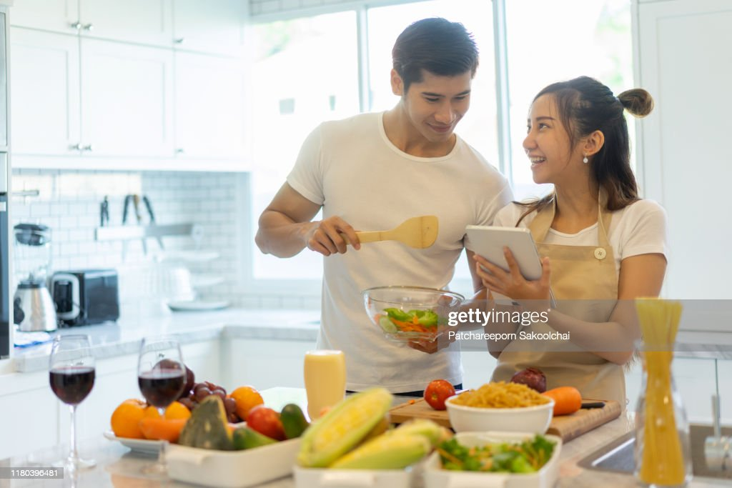 couple helping to cook in their kitchen : Stock Photo