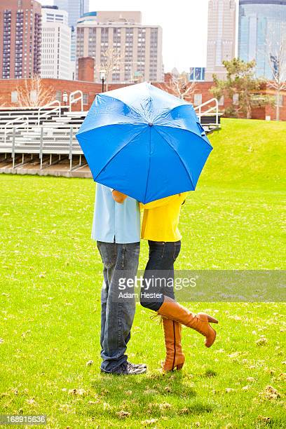 A couple hiding behind a umbrella outside.