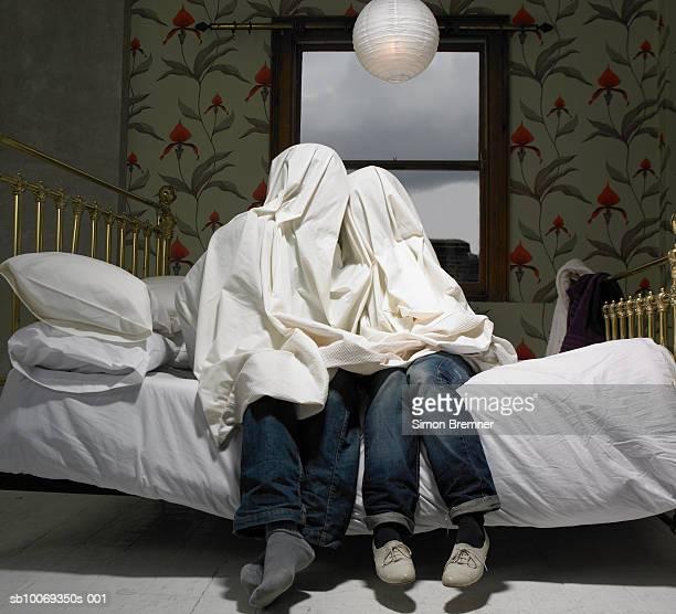 Paar versteckt unter Blatt auf Bett